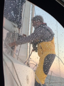 Brian tied in at mast taking the main down in 30 knot winds.