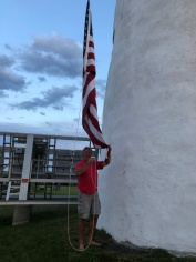 The flag being lowered at sunset